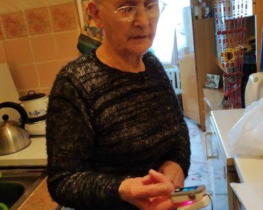 Seniorka, uczestniczka DDP stoi w kuchni, jest w trakcie badania saturacji i tętna. Przygląda się pulsoksymetrowi umieszczonemu na jej palcu