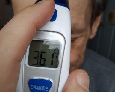 Senior, uczestnik DDP w czasie pomiaru temperatury ma przyłożony elektroniczny termometr do czoła. Na wyświetlaczu termometru widoczny jest wynik pomiaru