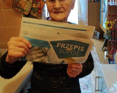 Uczestniczka DDP stoi w kuchni. W rękach trzyma egzemplarz gazety Przepis na Sopot