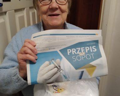Uczestniczka DDP stoi w drzwiach mieszkania, w rękach trzyma dostarczony obiad i egzemplarz gazety Przepis na Sopot