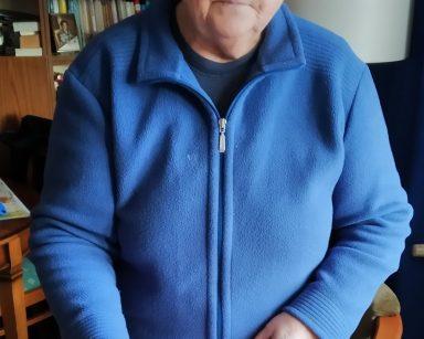 Seniorka, uczestniczka DDP w trakcie badania stoi z wyciągniętą ręką. Na palcu umieszczony ma pulsoksymetr