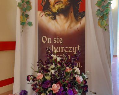 Dekoracja z fioletowymi, różowymi i białymi kwiatami z obrazem Chrystusa w koronie cierniowej