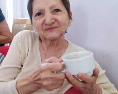 Na czerwonym fotelu siedzi seniorka w beżowym sweterku. W dłoniach trzyma białą filiżankę z kawą i uśmiecha się patrząc w obiektyw
