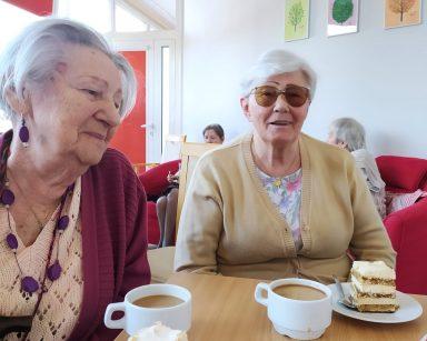 Przy stole siedzą dwie seniorki. Na drewnianym blacie przed nimi stoją białe filiżanki z kawą oraz białe talerzyki z ciastem tiramisu. Stół ozdobiony jest serwetką z różami o różowych płatkach i zielonych listkach. Na drugim planie w czerwonych fotelach siedzą dwie seniorki