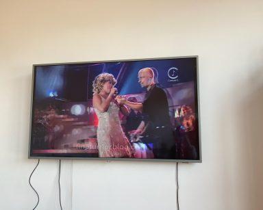 Na jasnej ścianie wisi płaski telewizor. W zatrzymanym ujęciu widać jak włoski piosenkarz Eros Ramazzotti śpiewa w duecie z amerykańską piosenkarką Tiną Turner