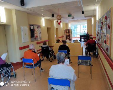 Na pierwszym planie seniorzy siedzą w trakcie nabożeństwa i odśpiewują pieśni. Na drugim planie muzyk Arkadiusz Wanat gra Gorzkie żale