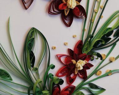 Obraz wykonany techniką quillingu. Na białym tle kwiaty o zielonych łodygach, czerwonych płatkach i żółtych środkach