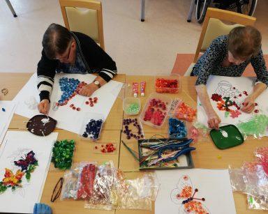 Widok z góry: seniorki pracują nad swoimi obrazkami. Na blacie rozłożone kartki, kleje, kolorowe papierowe paski i spiralki do wyklejania