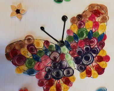 Obraz wykonany techniką quillingu. Na białym tle motyl ze skrzydłami z kolorowych papierowych spiralek, Obok kolorowe kwiatki