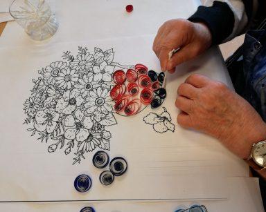 Widok z góry: dłonie seniora, który wykonuje obrazek techniką quillingu. Na białym tle wazon z czarnych i czerwonych papierowych spiralek oraz niedokończony bukiet kwiatów