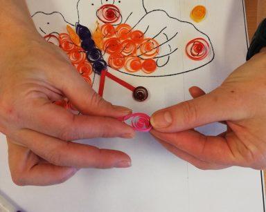 Na pierwszym planie dłonie osoby wykonującej obraz techniką quillingu. Na białym tle motyl ze skrzydłami z pomarańczowych, czerwonych i różowych papierowych spiralek