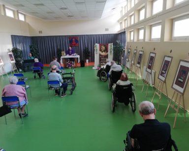 Seniorzy siedzą twarzami zwróconymi do ołtarza, uczestniczą w nabożeństwie. Wzdłuż ścian, na stelażach stoją tablice ze stacjami Drogi Krzyżowej. Na drugim planie widać ołtarz, przy którym ksiądz Krzysztof Rybka odprawia nabożeństwo, a obok Pan Arkadiusz Wanat siedzi przy pianinie