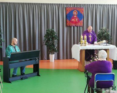 Seniorka siedzi i słucha nabożeństwa. Przy ołtarzu ksiądz Krzysztof Rybka odprawia nabożeństwo Drogi Krzyżowej, a obok Pan Arkadiusz Wanat siedzi przy pianinie i gra. W tle widać zawieszony obraz Chrystusa