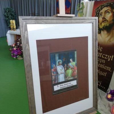Na drewnianym stelażu ze szklaną szybą stoi krzyż z rzymską cyfrą jeden. Za szybą obraz pierwszej stacji Drogi Krzyżowej, na którym Chrystus zostaje skazany na śmierć. W tle widać ołtarz i dekorację przedstawiającą Jezusa w koronie cierniowej
