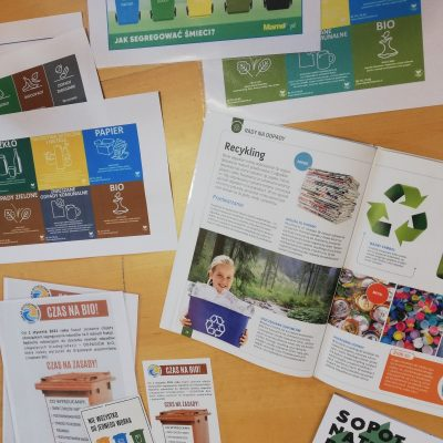 Widok z góry. Na blacie drewnianego stołu widać rozłożone czasopismo. Artykuł, który jest w nim zamieszczony opisuje recykling. Obok treści zamieszczone są zdjęcia: zielony las ze strumykiem, zgniecione puszki, nakrętki od butelek. Obok czasopisma widać kolorowe ulotki dotyczące segregacji odpadów. Pokazane jest, że odpady dzielimy na kategorie: szkło, papier, bio, tworzywa sztuczne, zmieszane, odpady zielone. Pojemnik lub worek na każdy rodzaj odpadów ma inny kolor