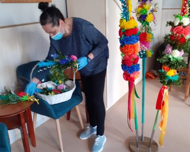 Fizjoterapeutka Magdalena Poraj-Górska nachyla się nad koszykiem z wielkanocnymi palmami z bukszpanu i bibuły. Obok na metalowej podstawce stoją trzy wysokie palmy. Są zrobione z kolorowych papierowych kwiatów