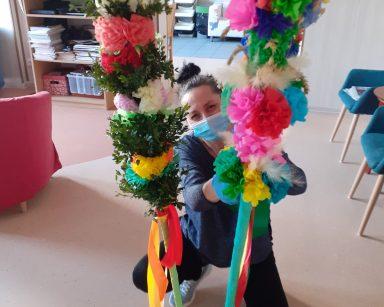 Fizjoterapeutka Magdalena Poraj-Górska przyklęka przed wielkanocnymi palmami. Palmy stoją na metalowej podstawce. Są zrobione z kolorowych papierowych kwiatów