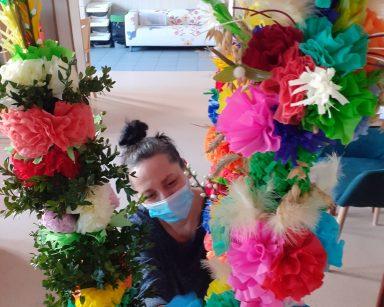Fizjoterapeutka Magdalena Poraj-Górska przyklęka przed wielkanocnymi palmami. Palmy są zrobione z kolorowych papierowych kwiatów