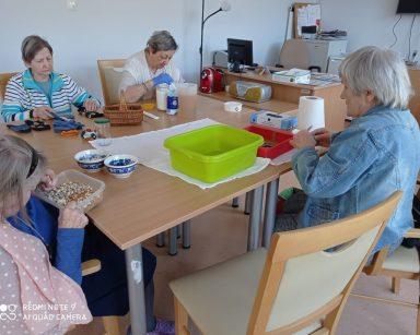Przy stole siedzą cztery seniorki i zajmują się drobnymi pracami. Seniorka w jeansowej bluzce wyciera sztućce. Obok siedzi seniorka z różową chustą w białe grochy. Przebiera nasiona i ziarna. Po drugiej stronie stołu seniorka w bluzce w kolorowe paski segreguje skarpety. Obok niej seniorka w białym sweterku miesza składniki na ciasto