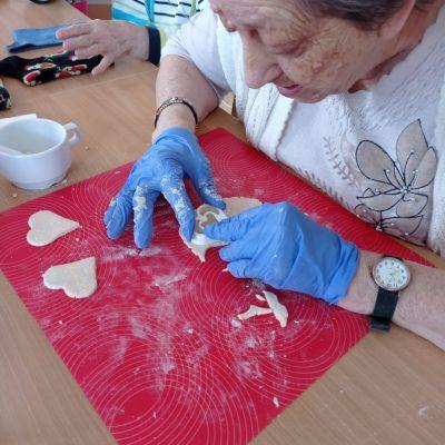 Seniorka siedzi przy stole. Na rękach ma nitrylowe niebieskie rękawiczki. Na czerwonej kuchennej macie wycina foremką serduszka z ciasta