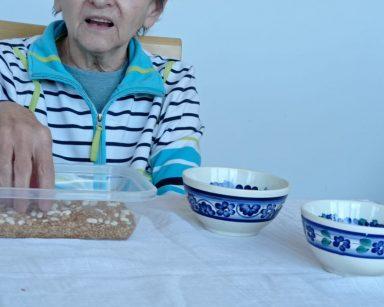 Seniorka siedzi przy nakrytym białym obrusem stole. Rozdziela fasolę i ziarna. Rozkłada je do dwóch niebiesko-białych misek