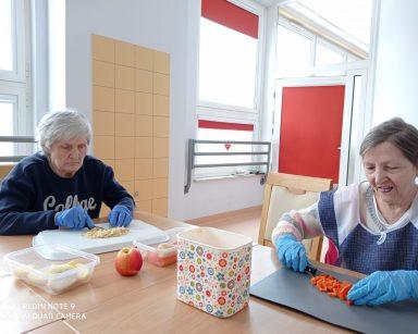 Seniorki siedzą przy stole. Na drewnianym blacie w plastikowych pojemnikach leżą jabłka, marchewki i pietruszka. Seniorki zajmują się ich krojeniem
