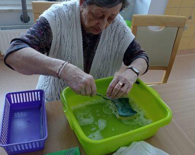 Seniorka siedzi przy stole i płucze sztućce w zielonej misce z wodą. Obok na zielonej serwetce leżą umyte widelce, noże i łyżki