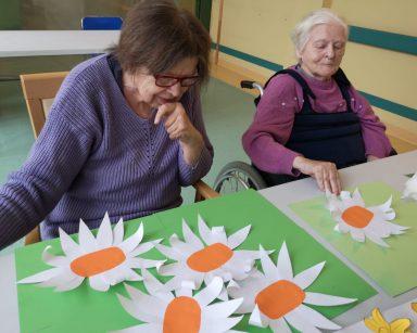 Dwie seniorki siedzą przy stole. Przed nimi na blacie leżą zielone kartki z naklejonymi papierowymi kwiatami o białych płatkach i pomarańczowych środkach