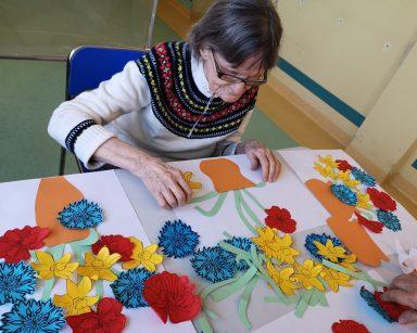 Seniorka siedzi przy stole. Pracuje nad swoim obrazem. Nakleja korony i łodygi kwiatów na białą kartkę z pomarańczowym wazonem. Na blacie leżą papierowe korony kolorowych kwiatów: czerwone maki, niebieskie chabry i żółte żonkile oraz prace innych uczestników
