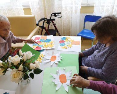 Trzy seniorki siedzą przy stole. Przed nimi na stole leżą obrazy z kwiatami: zielone kartki z naklejonymi papierowymi kwiatami o białych płatkach i pomarańczowych środkach oraz białe kartki z naklejonymi pomarańczowymi wazonami z papierowymi kwiatami o zielonych łodygach, żółtymi żonkilami, czerwonymi makami i niebieskimi chabrami