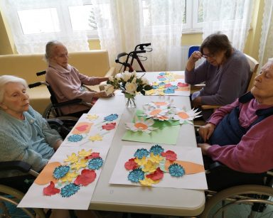 Cztery seniorki siedzą przy stole. Przed nimi na stole leżą obrazy z kwiatami: zielone kartki z naklejonymi papierowymi kwiatami o białych płatkach i pomarańczowych środkach oraz białe kartki z naklejonymi pomarańczowymi wazonami z papierowymi kwiatami o zielonych łodygach, żółtymi żonkilami, czerwonymi makami i niebieskimi chabrami
