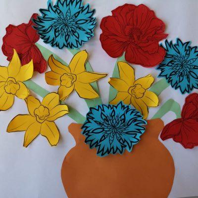 Obraz na białej kartce. Przedstawia naklejony pomarańczowy wazon pełen kwiatów z zielonymi łodygami, żółtych żonkili, czerwonych maków i niebieskich chabrów