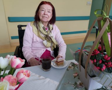 Przy stoliku siedzi odświętnie ubrana, uśmiechnięta seniorka. Przed nią na blacie stoi szklanka z kawą i talerzyk z kawałkiem ciasta. Obok widać różowe i białe tulipany oraz czerwone azalie w tekturowym koszyku