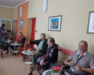 Czterech seniorów siedzi przy białych okrągłych stolikach. Na blatach stoją małe wazony z różowymi kwiatami. Każdy z seniorów ma szklankę z kawą i talerzyk z kawałkiem ciasta
