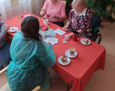 Przy stole siedzi makijażystka Marta i rozmawia wraz z siedzącymi na przeciwko i obok seniorkami. Stół jest nakryty czerwonym obrusem. Na blacie stoi wazon z różowymi kwiatami, szklanki z kawą i talerzyki z kawałkami ciasta