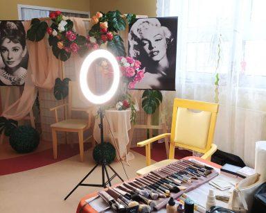 Kącik do robienia makijażu. Ściana jest udekorowana kwiatami i portretem Marilyn Monroe. Na stoliku stoi wazon z białymi, różowymi i czerwonymi kwiatami. Obok znajduje się profesjonalna lampa do robienia makijażu. Przy niej stoi krzesło oraz stół z przyborami do malowania i pielęgnacji