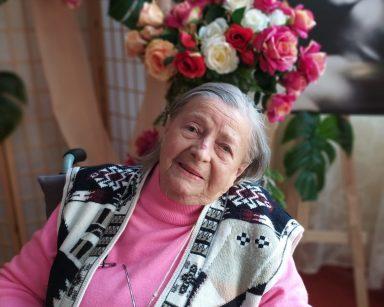 Na pierwszym planie siedzi uśmiechnięta seniorka. W tle widać dekoracje z kwiatów i czarno-biały portret Marilyn Monroe