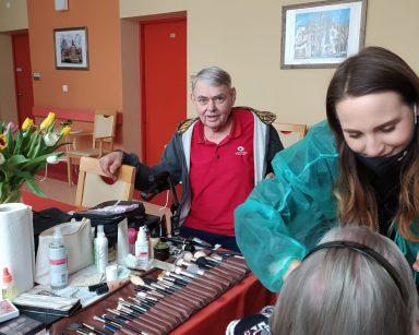 Makijażystka Marta nachyla się nad seniorką i robi jej makijaż. Z tyłu widać seniora siedzącego przy stole. Na stole leżą przybory do makijażu