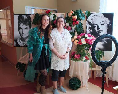 Makijażystka Marta pozuje z seniorką do zdjęcia. Obie Panie są uśmiechnięte. Stoją przy stoliku z wazonem pełnym białych, różowych i czerwonych kwiatów. Za nimi widać girlandy z kolorowych kwiatów oraz czarno-białe zdjęcia Marilyn Monroe i Audrey Hepburn