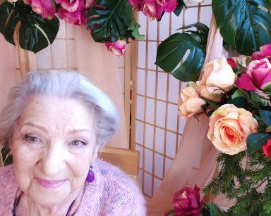 Na krześle siedzi uśmiechnięta seniorka. Ma na sobie różowy sweterek i kolorystycznie dobrany makijaż. W tle widać dekorację z zielonych gałązek, białych, czerwonych, różowych i kremowych róż
