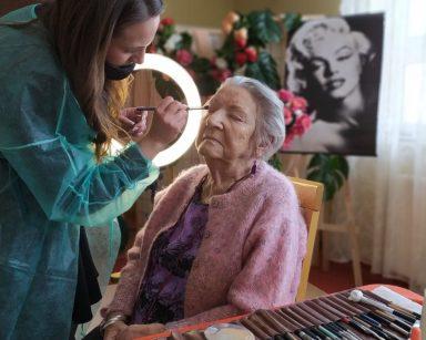 Makijażystka Marta pochyla się nad siedzącą na krześle seniorką. W ręce trzyma pędzelek i nakłada nim kolorowy cień na powiekę. Przed nimi na stole leżą pędzle do makijażu i kosmetyki