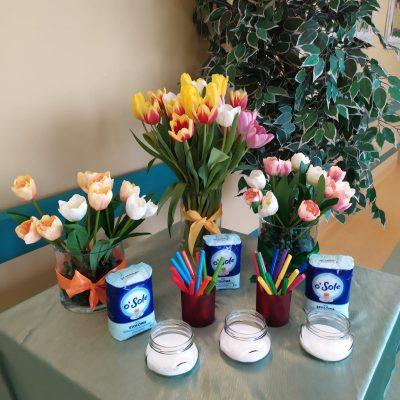 Na stoliku leży zielony satynowy obrus. Na blacie widać trzy przezroczyste słoiczki z białą solą. Za nimi stoją dwa bordowe kubki z kolorowymi mazakami. Następnie ustawione są trzy niebieskie opakowania soli. Z tyłu widać trzy szklane wazony z białymi, kremowymi, żółtymi i różowymi tulipanami
