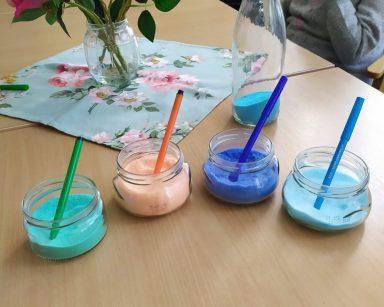 Na blacie stoją cztery przezroczyste słoiczki z kolorową solą: zieloną, pomarańczową, granatową, błękitną i kolorystycznie dobranymi mazakami. Za nimi stoi szklany wazon z białymi oraz różowymi kwiatami i butelka częściowo napełniona granatową solą. W tle widać siedzących przy stole seniorów