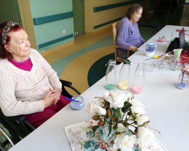 Przy stole siedzi seniorka. Przed nią na blacie leży przezroczysty słoiczek z niebieską solą. Obok siedzi druga seniorka. Przed nią na blacie leży słoiczek z różową solą. Na białym stole widać trzy szklane butelki częściowo napełnione kolorową solą, pojemnik z solą, kolorowe mazaki, wazon z białymi różami