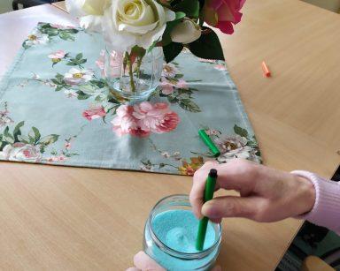 Na drewnianym blacie leży zielona serwetka w różowe kwiaty. Na niej stoi wazon z białymi i różowymi kwiatami. Przy brzegu blatu widać ręce seniorki. Jedną ręką przytrzymuje słoiczek z zieloną solą, w drugiej trzyma zielony mazak