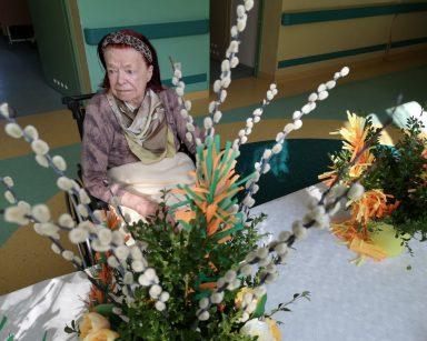Przy stole siedzi seniorka. Przed nią na blacie stoją wazony z wielkanocnymi palmami. Palmy wykonane są z kolorowej bibuły, gałązek bazi i bukszpanu