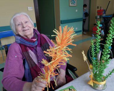 Przy stole siedzi uśmiechnięta seniorka. W ręku trzyma wielkanocną palmę z kolorowej bibuły