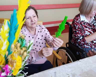 Przy stole siedzi uśmiechnięta seniorka. Robi wielkanocną palmę z zielonej bibuły. Obok widać druga seniorkę