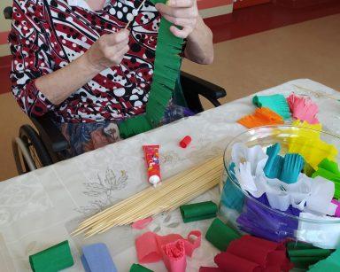 Przy stole siedzi uśmiechnięta seniorka. Robi wielkanocną palmę z kolorowej bibuły. Przed nią na blacie leżą elementy do wykonania palem: kolorowa bibuła, drewniane patyczki, klej