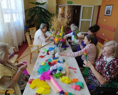 Seniorki siedzą przy stole. Przygotowują palmy wielkanocne z papierowych kwiatów, świeżych gałązek bazi i bukszpanu. Wraz z nimi siedzi terapeutka Anna Rzepczyńska